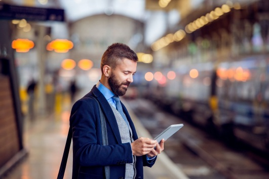 man at train station with tablet